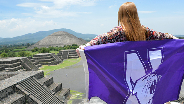 Student with Wildcat flag at a temple in Furuya, Mexico